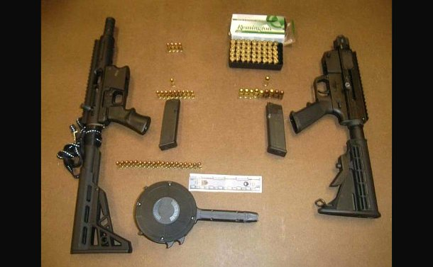 Two long black guns with bullets on a table
