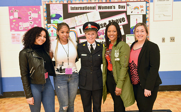 One woman in TPS uniform with four other women