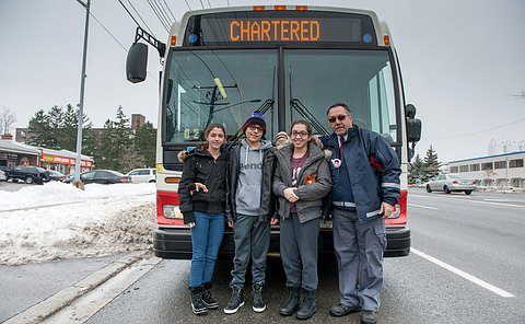 An TTC official in uniform in front of a bus with three teenagers.