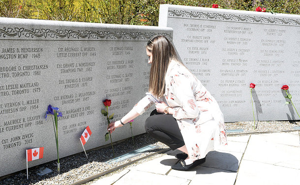 Woman kneeling in-front of a monument placing a red rose on it