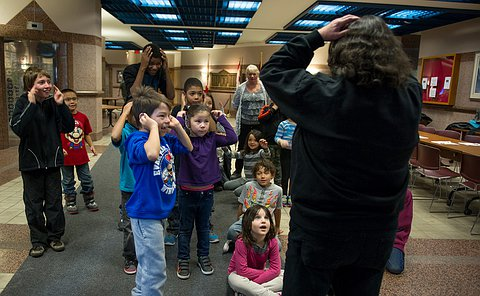 A dozen young children sitting and standing looking up at a woman who is moving animatedly. The woman's back is to the camera and the children are facing the camera.