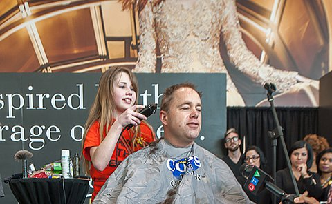 A seated man has his head shaved by a girl as he speaks into a microphone