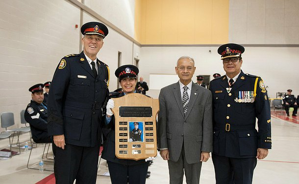 A woman with an award shield in her hands, to her right is the chief, to her left the Chair and Superintendent.