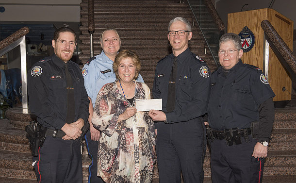 A group of people, some in TPS uniform, a woman holds a cheque