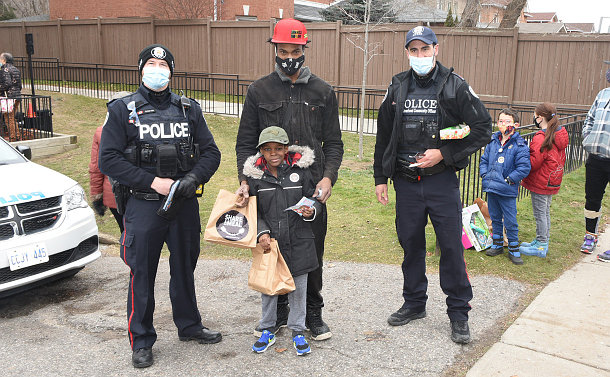 Police officers and a man and boy with brown bags