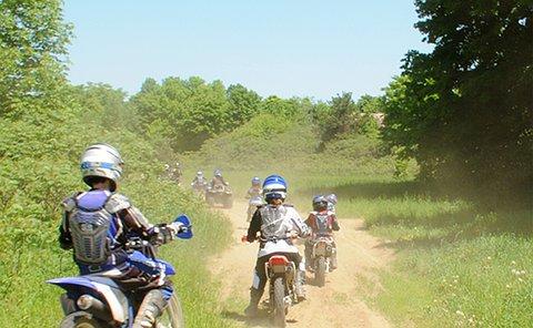 A group of dirt bikes rides along a dirt path
