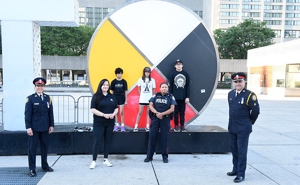 A group of people, some in TPS uniform in front of a large medicine wheel