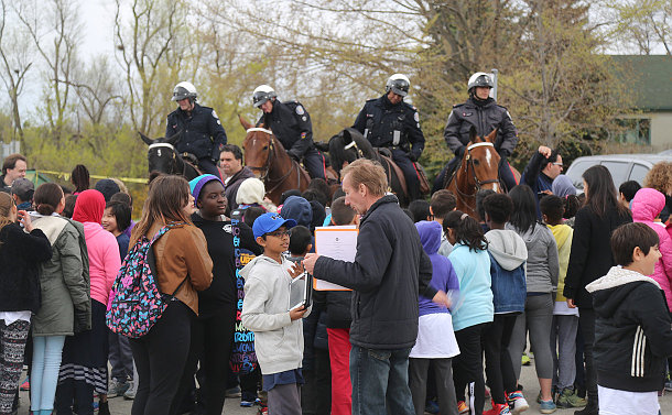 Four Mounted unit officers on horses behind a large group of kids