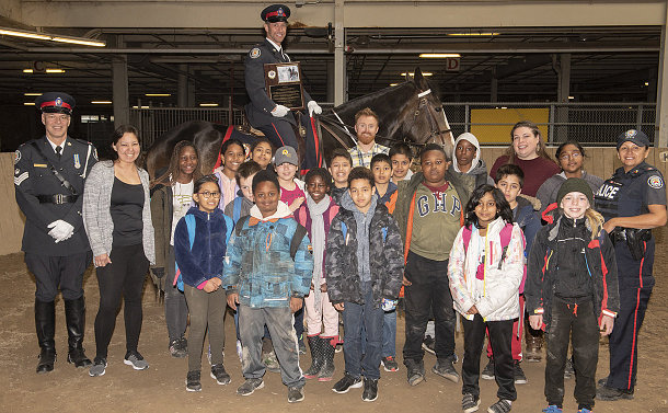 A group of kids and police officers in front of a horse