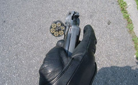 A gloved hand hold a revolver with the chamber open