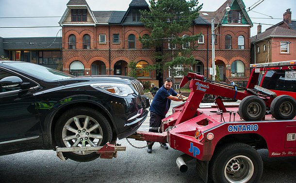 A tow truck driver between a tow truck and a car using hand levers