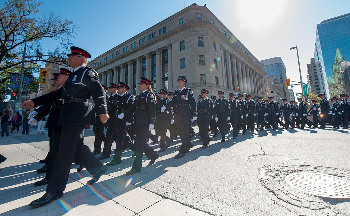 A line of officers marching on a street