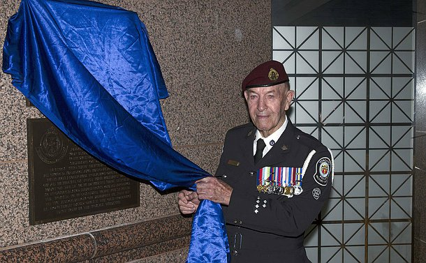 A man wearing a police uniform with many decorations unveils a plaque covered with blue robe
