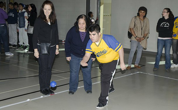 A young man in a jersey underhand throws a ball in a gym as people watch