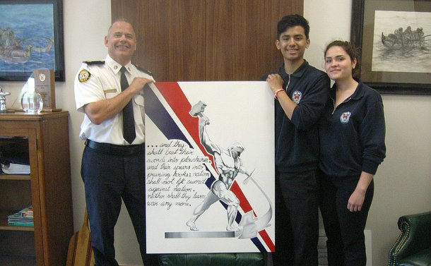 A man in TPS uniform holds a painting alongside a teenage boy and girl