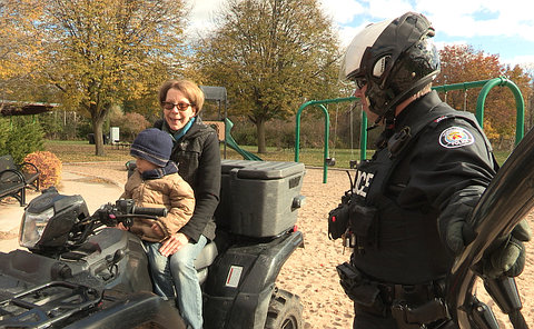 A man in TPS uniform talking with a woman and child seated on an ATV