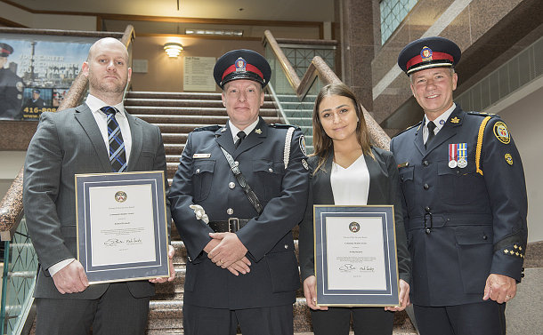 Two men in TPS uniform with a man and a woman holding framed certificates