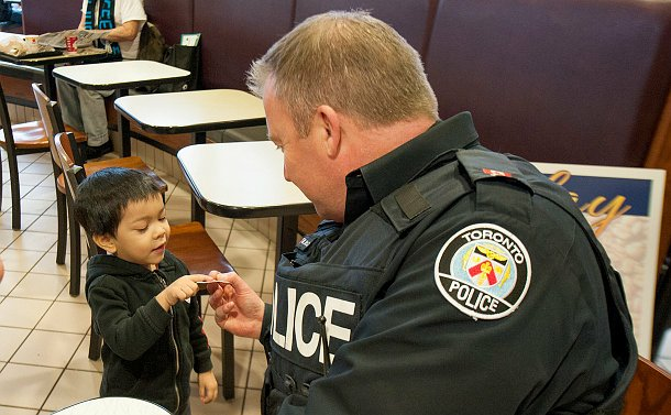 A toddler taking a sticker from an officer in uniform