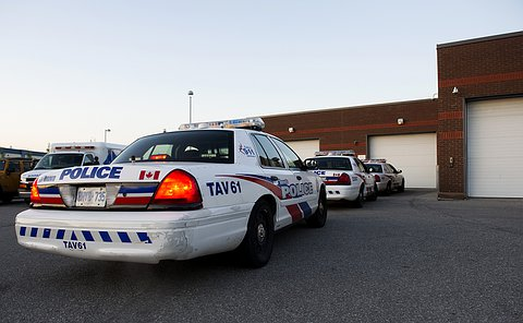 Three marked TPS vehicles wait in a line beside garage doors