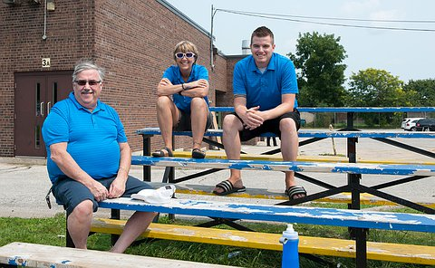 There people sit on blue and yellow bleachers, smiling. They are all wearing blue shirts.