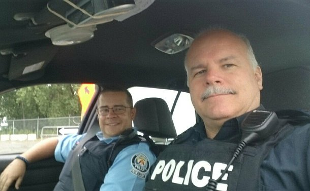 Two men seated in a TPS scout car, one in TPS Auxiliary uniform and one TPS uniform