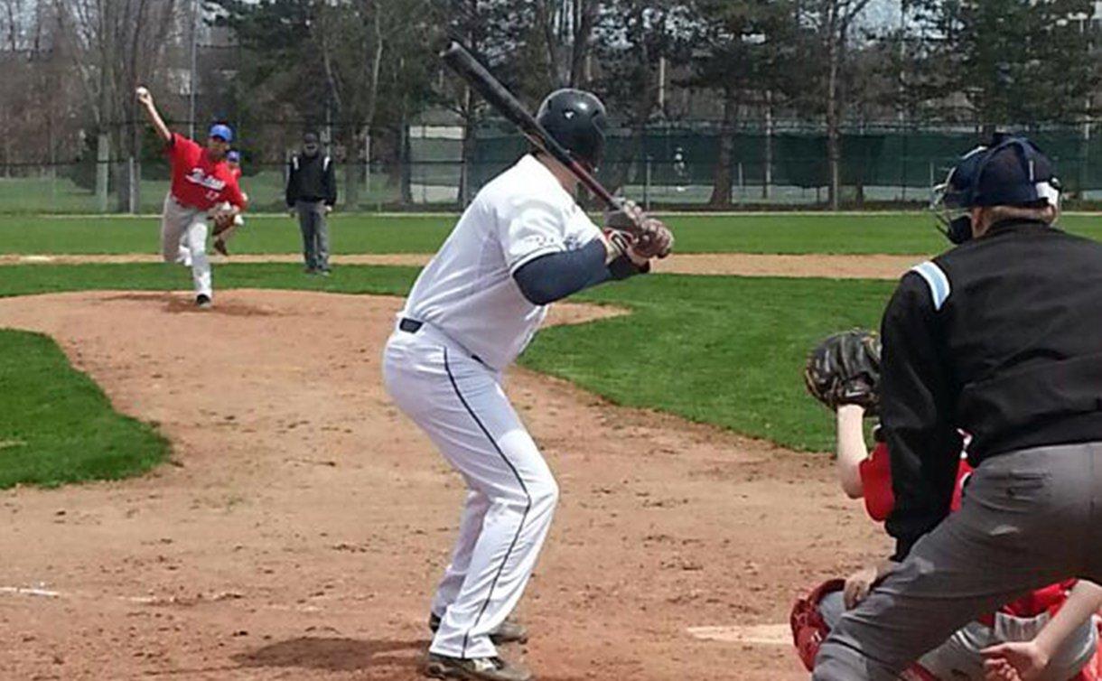 A pitcher throws a ball as a batter, catcher and umpire await