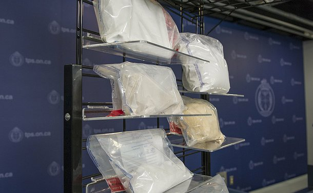 A metal rack with various white and brown substances in plastic bags