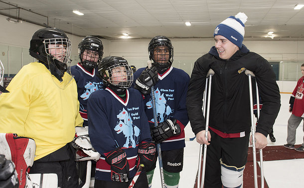 A boy on crutches speaks to younger boys in hockey uniform