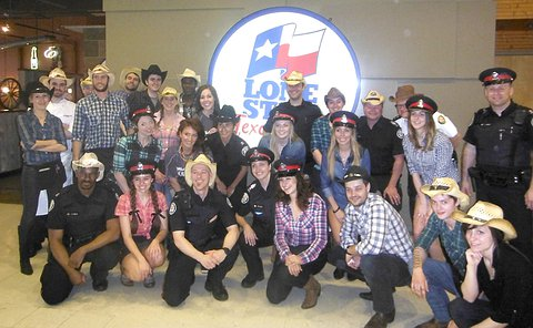 A group photo of several dozen people wearing cowboy hats and shirts and in TPS uniform
