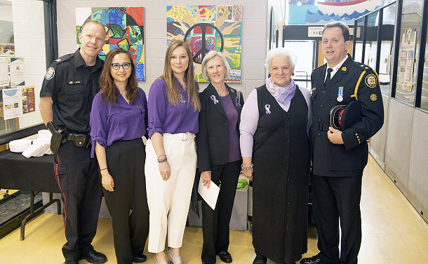 Four women are flanked by two men in police uniforms