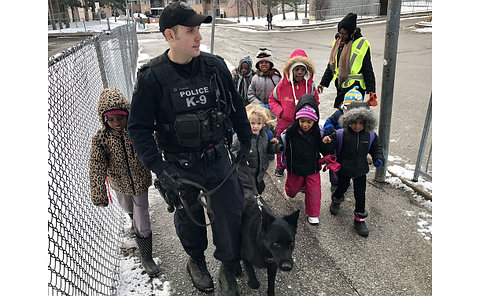 Children walking with a police officer and a K9 dog officer.