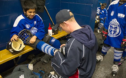 A man kneels in front of a boy in hockey uniform tying his laces on his skates
