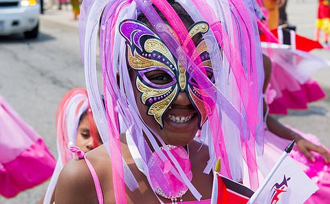 An extreme close up of a young girl smiling, wearing a pink and purple mask with streamers and feathers.