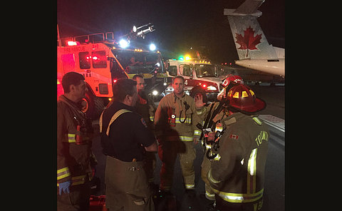 A group of firefighters huddle near a plane