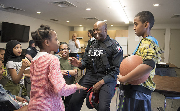 A man in TPS uniform talking to children