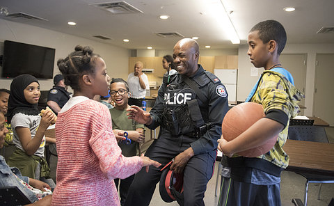 A man in TPS uniform talking to children