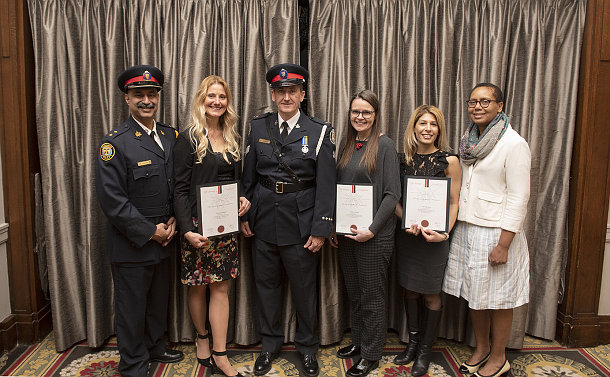 Two men in TPS uniform with four women