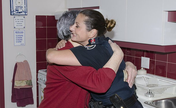 A woman hugs another woman in a Toronto Police uniform in a kitchen setting