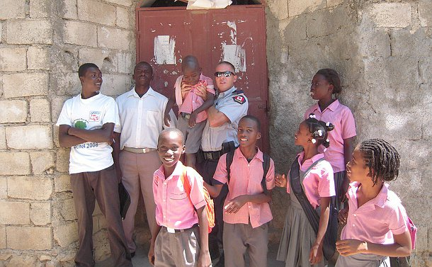 A man in police uniform with two other men and girls and boys in school uniform