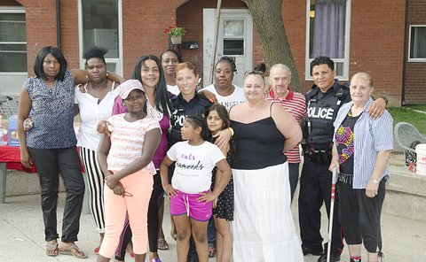 A man and woman in TPS uniform with a group of people