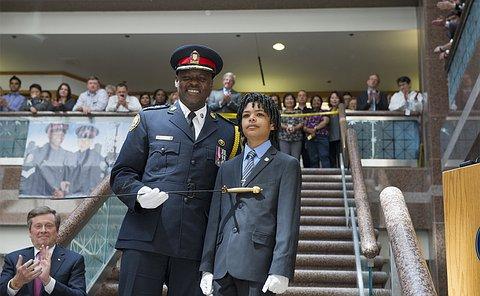 A man in TPS uniform holding a sword beside a boy