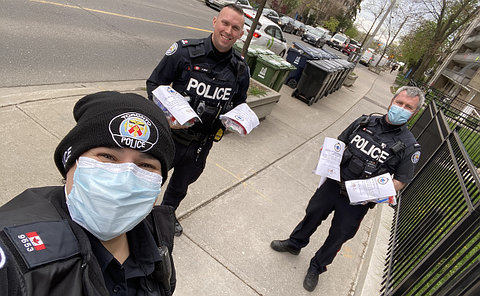 Three officers in TPS uniforms with care packages