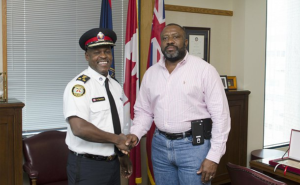 A man in TPS uniform shakes the hand of another man
