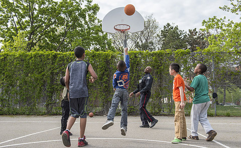 men in TPS uniform playing on a court with kids
