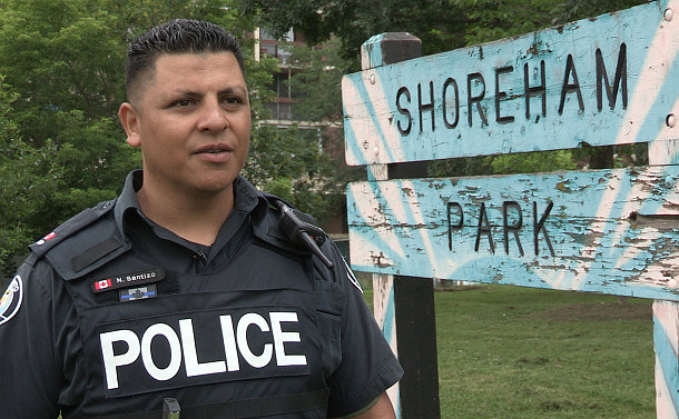 A man in TPS uniform beside a Shoreham Park sign