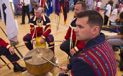 Three men drum together
