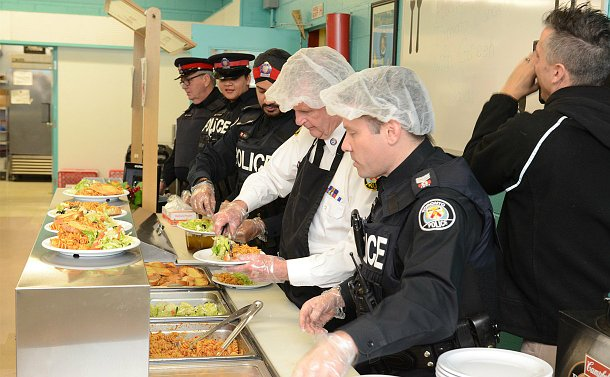 A row of men and women in TPS uniform dish up food behind a counter