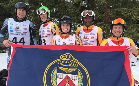 People in ski helmets holding a TPS flag