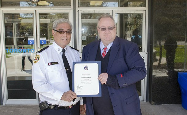 A man in TPS uniform holding a certificate beside a man in TTC uniform