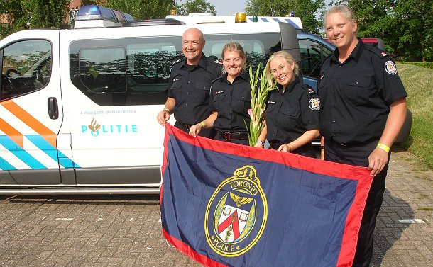 A man and three women all wearing police uniforms and holding a flag with a Toronto Police Service crest standing next to a Dutch police van